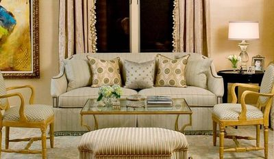 Photo by Gin Hunt Designer Sharon Kleinman, owner of Transitions in Potomac, shows how adding decorative trim to various items in a room, such as window treatments, the sofa and ottoman, can create a more luxurious look.