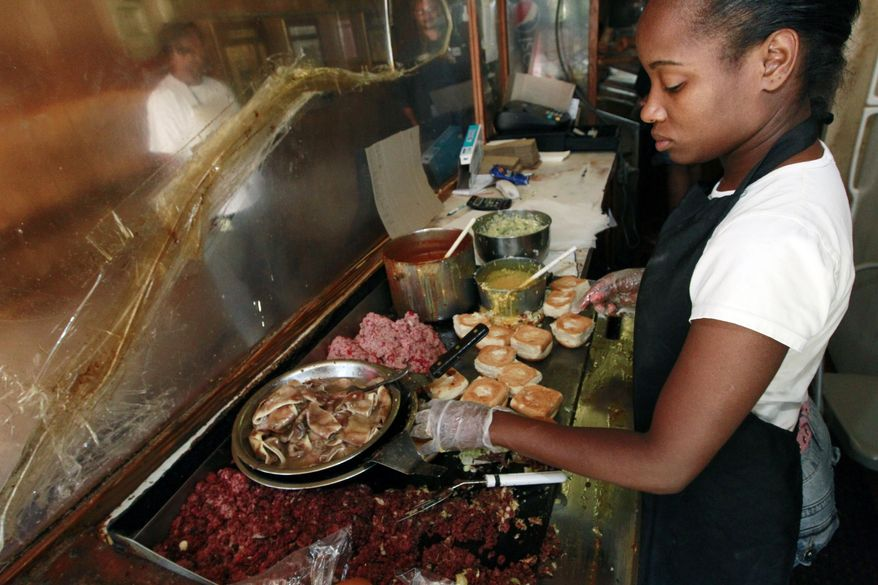 """**FILE** Big Apple Inn grill cook Tyechia Davis prepares the sausage meat for a """"smoke"""" sandwich in Jackson, Miss., on May 29, 2012. (Associated Press)"""