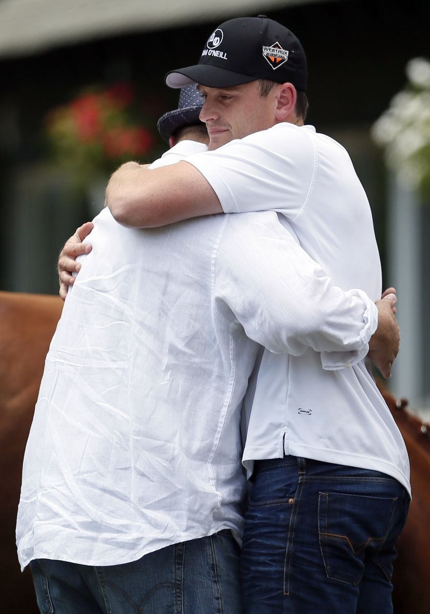 Jack Sisterson, right, assistant trainer for Kentucky Derby and Preakness winner I'll Have Another, hugs trainer Doug O'Neill after a news conference at Belmont Park in Elmont, N.Y., on Friday, June 8, 2012. I'll Have Another's bid for a Triple Crown ended with the shocking news that the colt was out of the Belmont Stakes due to a swollen left front tendon. The Belmont Stakes is Saturday. (AP Photo/Patrick Semansky)