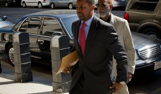 Former D.C. Council Chairman Kwame R. Brown (left) enters the E. Barrett Prettyman Federal Courthouse for his plea hearing in Washington, D.C., Friday, June 8, 2012. (Rod Lamkey Jr/The Washington Times)