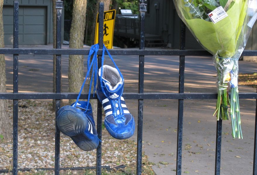 Wrestling shoes and flowers left by friends and neighbors hang June 7, 2012, from the fence of the home of Ron and Rebecca Bramlage and their four children in Junction City, Kan. The family died in a Florida plane crash, and three Bramlage boys were wrestlers. (Associated Press)