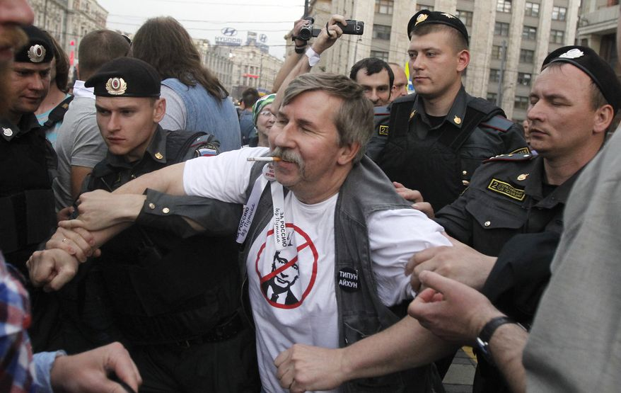 **FILE** Russian police detain a protester June 6, 2012, near the Kremlin in Moscow. Russian President Vladimir Putin has taken a harder line against the opposition since returning to the presidency a month ago. (Associated Press)