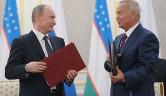 Uzbekistan President Islam Karimov (right) and Russian President Vladimir Putin exchange documents June 4, 2012, after their talks in Tashkent, the capital of Uzbekistan. Putin and Karimov signed the Declaration of Enhanced Strategic Partnership between the two countries and the Memorandum of Understanding at their talks in Tashkent. (Associated Press/RIA-Novosti, Alexei Druzhinin, Presidential Press Service)