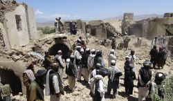 Villagers gather at a house destroyed in an apparent NATO raid in Logar province, south of Kabul, Afghanistan, on Wednesday, June 6, 2012. Afghan officials and residents say the airstrike, aimed at militants, killed civilians celebrating a wedding, including women and children. (AP Photo/Ihsanullah Majroh)