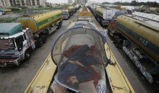 A man in Karachi, Pakistan, naps on Thursday, May 17, 2012, on one of the oil tankers used to transport NATO fuel supplies to neighboring Afghanistan. Pakistan closed the supply route to Afghanistan after American airstrikes killed 24 Pakistani troops along the Afghanistan-Pakistan border in November. (AP Photo/Fareed Khan)