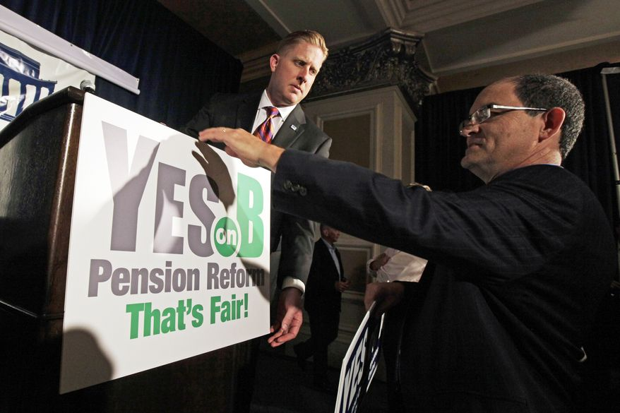 Supporters of Proposition B, which would roll back public pensions, adjust a sign before a rally on election day in San Diego on Tuesday, June 5, 2012. (AP Photo/Gregory Bull)