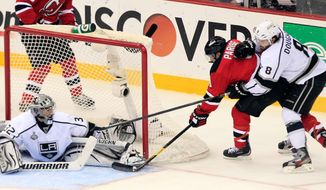 New Jersey's Zach Parise jams the puck past Los Angeles goalie Jonathan Quick for the Devils' first goal in their 2-1 win Saturday. New Jersey has won two straight after dropping the first three in the Stanley Cup Final. Game 6 is Monday night. (Associated Press)