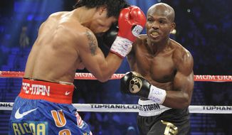 Manny Pacquiao covers up as Timothy Bradley throws a punch in the first round of their WBO world welterweight title fight Saturday, June 9, 2012, in Las Vegas. Bradley won a split decision. (AP Photo/Chris Carlson)