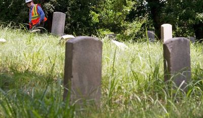 Bill Willis of the General Services Administration examines graves of Civil War soldiers - from the Confederacy and the Union - on the grounds of the former St. Elizabeths Hospital in the District on Thursday. (Barbara L. Salisbury/The Washington Times)