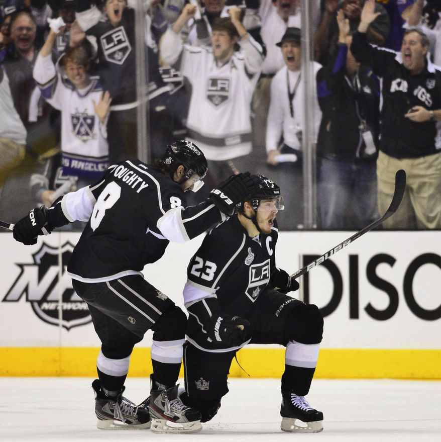 Los Angeles Kings right wing Dustin Brown (23) and Los Angeles Kings defenseman Drew Doughty (8) celebrate after Brown scored his second goal of the first period against the New Jersey Devils during Game 6 of the NHL Stanley Cup finals, Monday, June 11, 2012, in Los Angeles. The Kings won the game, 6-1, to win the Stanley Cup. (AP Photo/Mark J. Terrill)