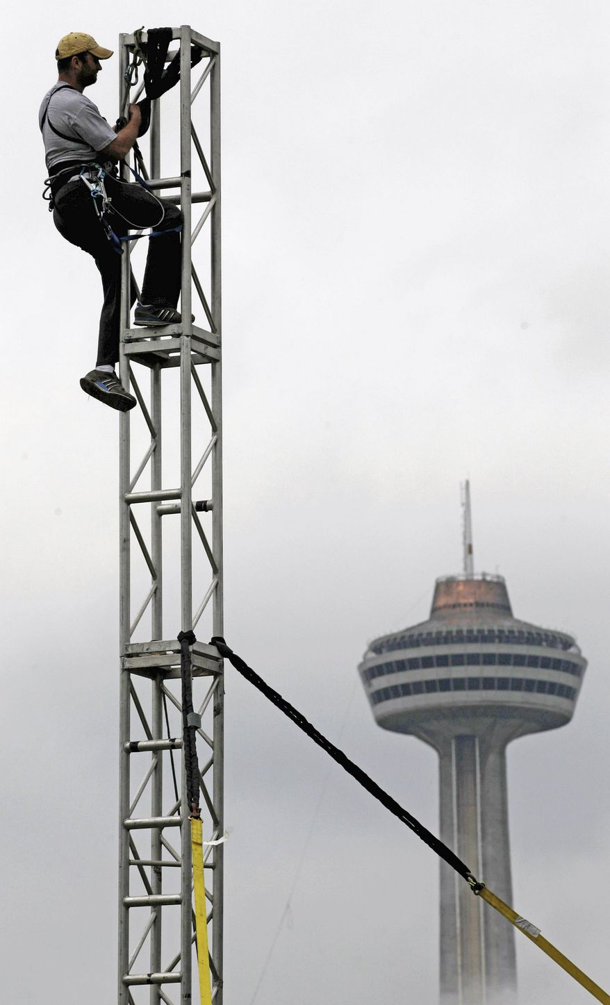 Scott O'Shea rigs a tower in preparation for Nik Wallenda's tightrope walk in Niagara Falls, N.Y., this week. Mr. Wallenda estimates his U.S.-to-Canada walk by way of a cable strung over the brink will cost $1.2 million to $1.3 million. (Associated Press)