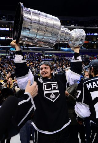 Los Angeles center Andrei Loktionov hoists the Stanley Cup after the Kings defeated the New Jersey Devils in six games. (Associated Press)
