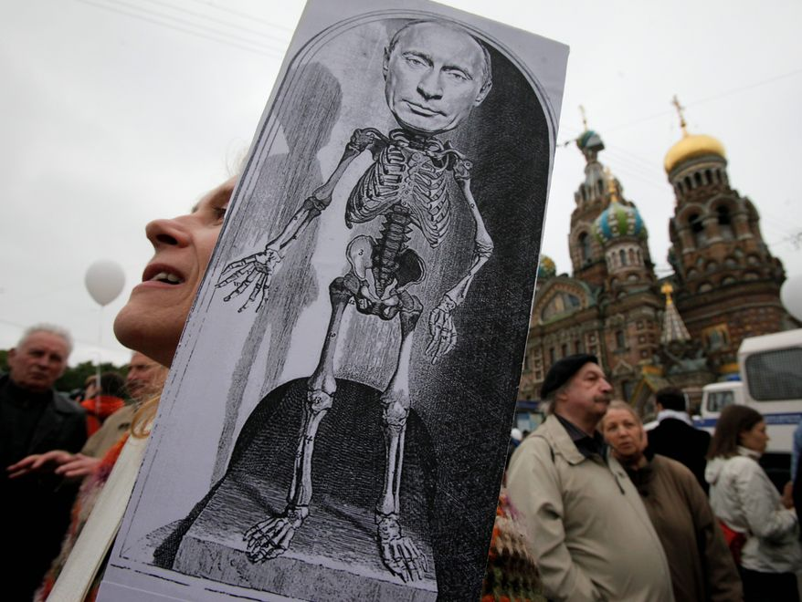 A woman holds a caricature depicting Russian President Vladimir Putin during an opposition rally in St. Petersburg, Russia, on Tuesday. The rally came a day after policed raided the homes of protest leaders. Opposition figures likened the raids to the repression of Soviet dictator Josef Stalin. (Associated Press)