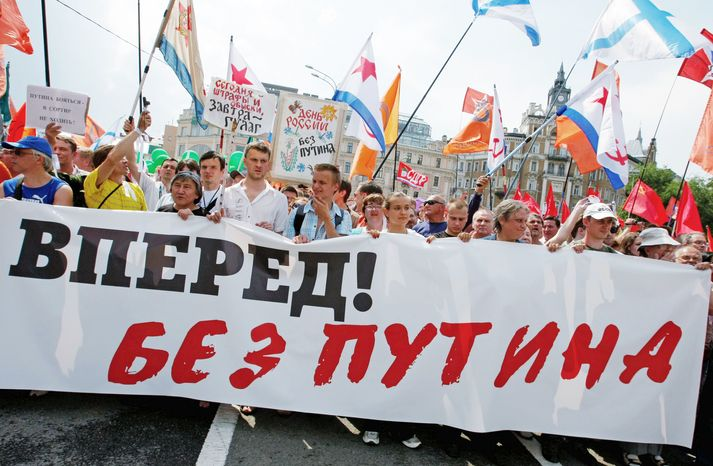 """Protesters carry a message reading """"Russia Go Forward Without Putin"""" as thousands of people rally in Moscow on Tuesday, the Russia Day holiday marking the declaration of independence from the Soviet Union in 1990. (Associated Press)"""