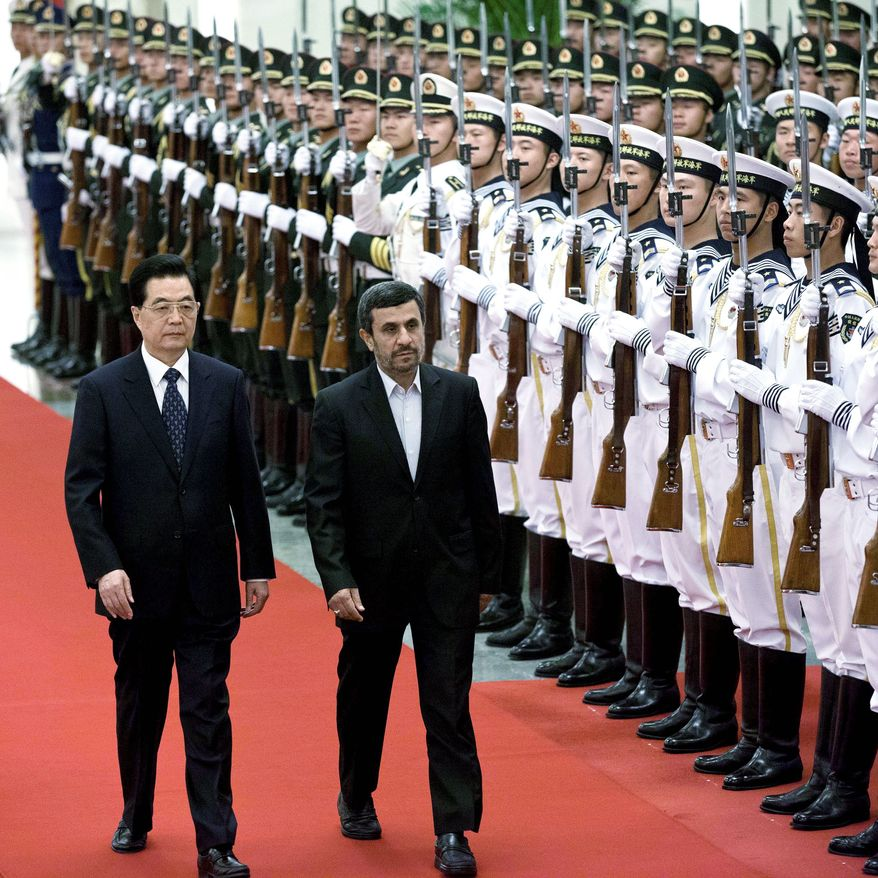 Iranian President Mahmoud Ahmadinejad (right)and Chinese President Hu Jintao review an honor guard during a welcoming ceremony Friday at the Great Hall of the People in Beijing. Mr. Ahmadinejad held more sway at a security summit in China than he does with Iran's theocracy at home. (Associated Press)