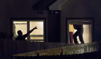 Law enforcement officials search a house in Montgomery, Ala., on Monday, June 11, 2012, for Desmonte Leonard, who is wanted in the shooting deaths of three men near Auburn University on Saturday night. (AP Photo/Dave Martin)