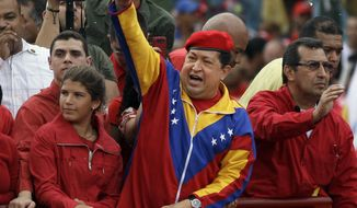 Venezuelan President Hugo Chavez (center) acknowledges the crowd from atop a truck upon his arrival at the elections commission offices in Caracas, Venezuela, on Monday, June 11, 2012, to formalize his re-election bid. (AP Photo/Ariana Cubillos)