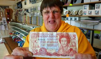 ** FILE ** Sybie Summers, owner of the Pod gift shop in Stanley, Falkland Islands, holds up a 5-pound local banknote with an illustration of Britain's Queen Elizabeth II on Sunday, March 4, 2012. (AP Photo/Michael Warren)