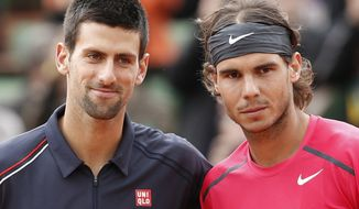 Rafael Nadal of Spain and Novak Djokovic of Serbia pose for photographers ahead of the final match at the French Open tennis tournament in Roland Garros stadium in Paris on Monday, June 11, 2012. Rain suspended the final, which was won by Nadal, making it the first French Open not to end on Sunday since 1973. (AP Photo/Bernat Armangue)