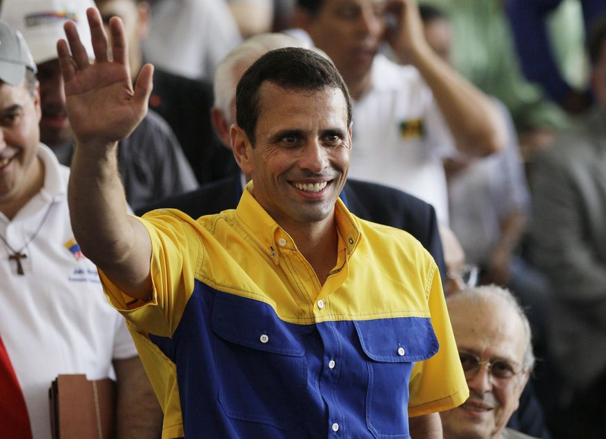 Opposition candidate Henrique Capriles waves during a ceremony to register his candidacy for the Venezuelan presidency in Caracas, Venezuela, on Sunday, June 10, 2012. (AP Photo/Ariana Cubillos)