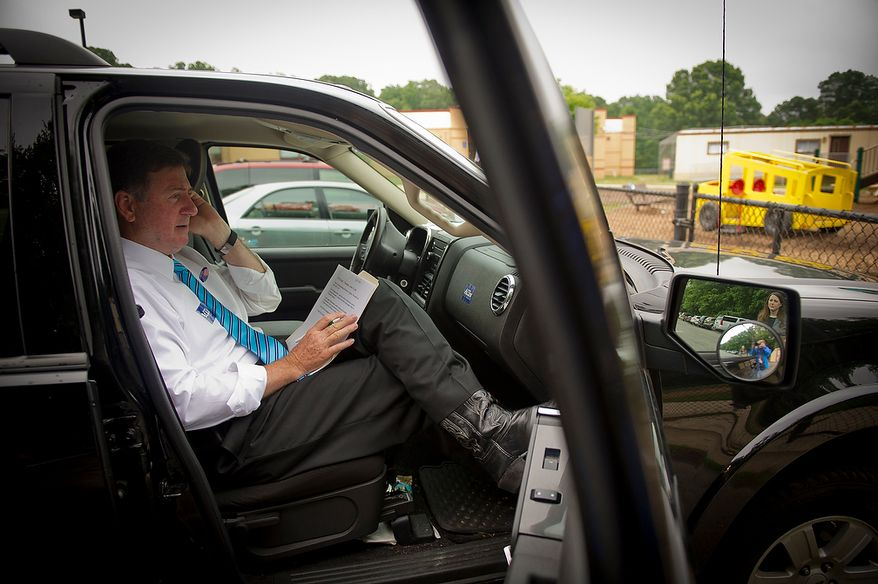 Former Virginia Governor and Republican U.S. Senate candidate George Allen gives an interview on his phone as he sits back in his SUV at the Orange Hunt Elementary School precinct in Springfield, Va., Tuesday, June 12, 2012. (Rod Lamkey Jr/The Washington Times)