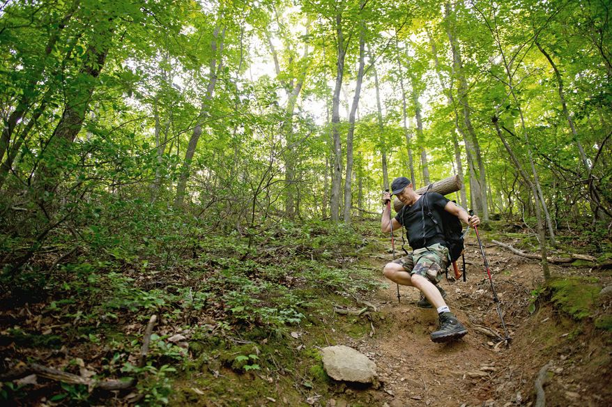 """Mike Canino of Tyson's Corner, Va., straps a log he has named """"Larry"""" to his backpack and hikes up and down steep terrains while training at the Scott's Run Nature Preserve for the Spartan Death Race, a tortuous combination of forced hikes, obstacle courses, sleep deprivation, and mental strain that is held annually in Vermont, McLean, Va., Sunday, June 10, 2012. (Andrew Harnik/The Washington Times)"""
