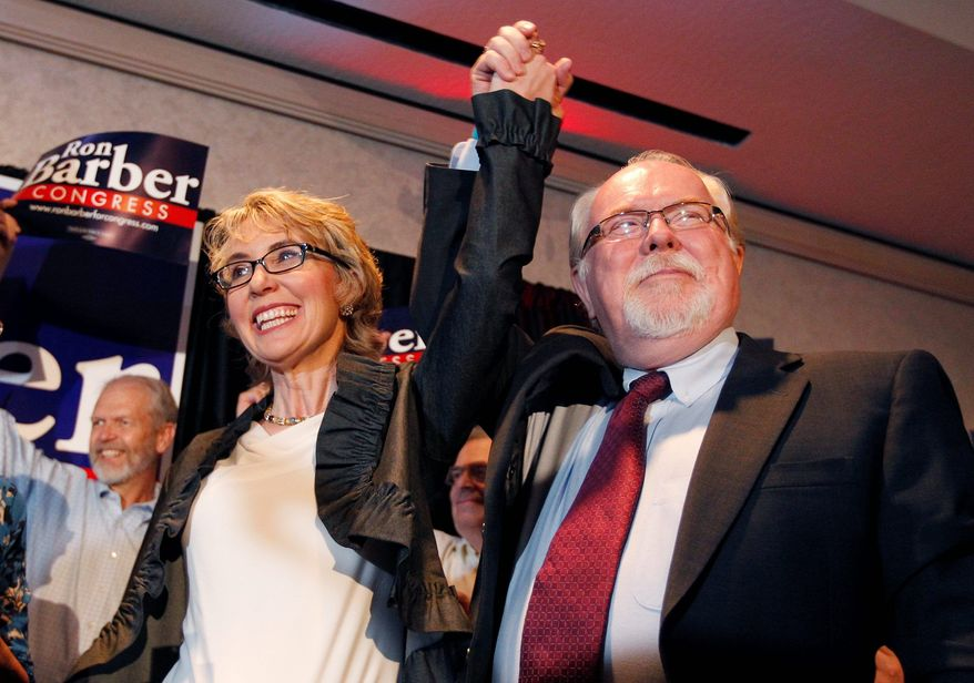 Democratic candidate Ron Barber celebrates his victory in a special election in Arizona Tuesday with Gabrielle Giffords, the congresswoman he succeeds, by his side. Mr. Barber easily topped Republican Jesse Kelly in a race in which both parties tested themes that will play out in the November election. (Associated Press)