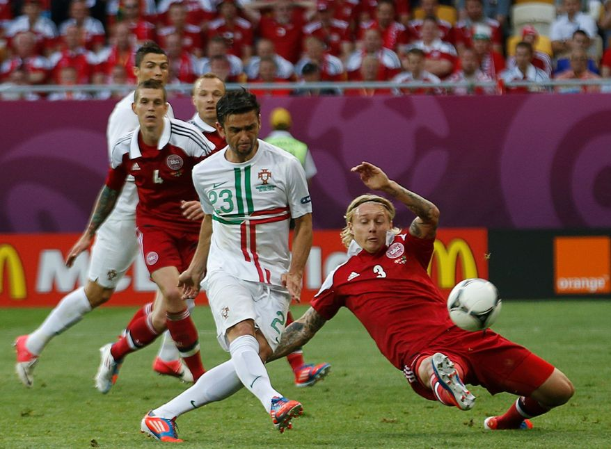 Portugal's Helder Postiga (23) scores past Simon Kjaer during a 3-2 victory over Denmark in Euro 2012 Group B match. Portugal blew a two-goal lead before the win. (Associated Press)