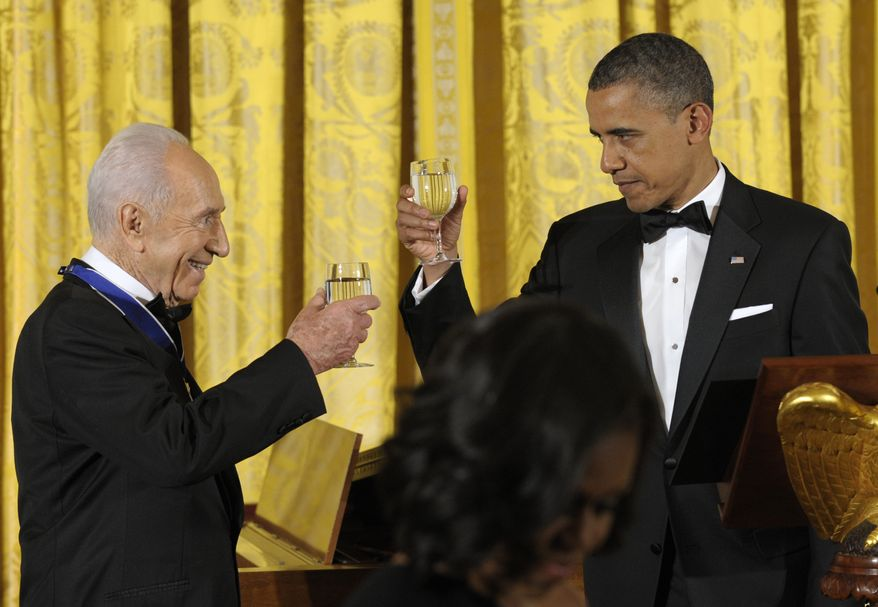 ** FILE ** President Obama and Israeli President Shimon Peres share a toast after Mr. Obama presented Mr. Peres with the Presidential Medal of Freedom at a dinner in the East Room of the White House in Washington on Wednesday, June 13, 2012. (AP Photo/Susan Walsh)