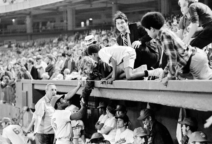 FILE - In this Sept. 30, 1971 file photo,  Washington Senator fans lean over the dugout to shake hands with Washington's Dave Nelson (15) before fans storm the field in the ninth inning of the Washington Senators farewell appearance at RFK Stadium.  (AP Photo/File)