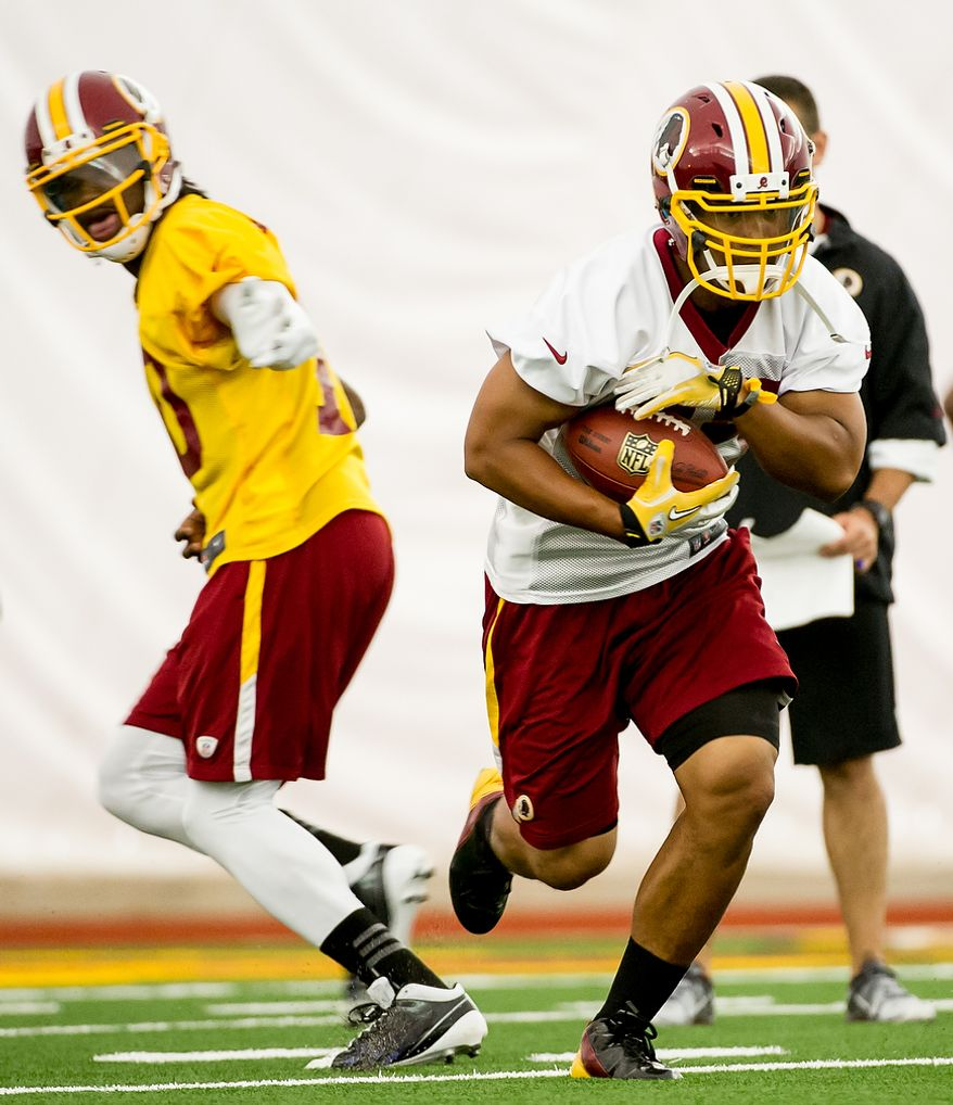 Washington Redskins quarterback Robert Griffin III (10), left, hands off to Washington Redskins running back Evan Royster (35), right, in the team's indoor training facility during mini camp at Redskins Park, Ashburn, Va., Tuesday, June 12, 2012. (Andrew Harnik/The Washington Times)