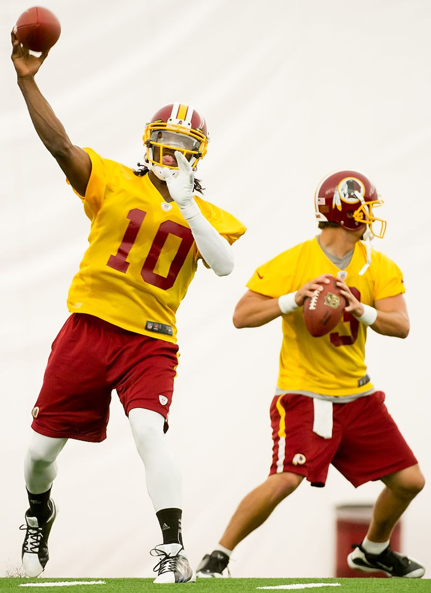 Washington Redskins quarterback Robert Griffin III (10), left, and Washington Redskins quarterback Jonathan Crompton (3), right, complete passes in the team's indoor training facility during mini camp at Redskins Park, Ashburn, Va., Tuesday, June 12, 2012. (Andrew Harnik/The Washington Times)