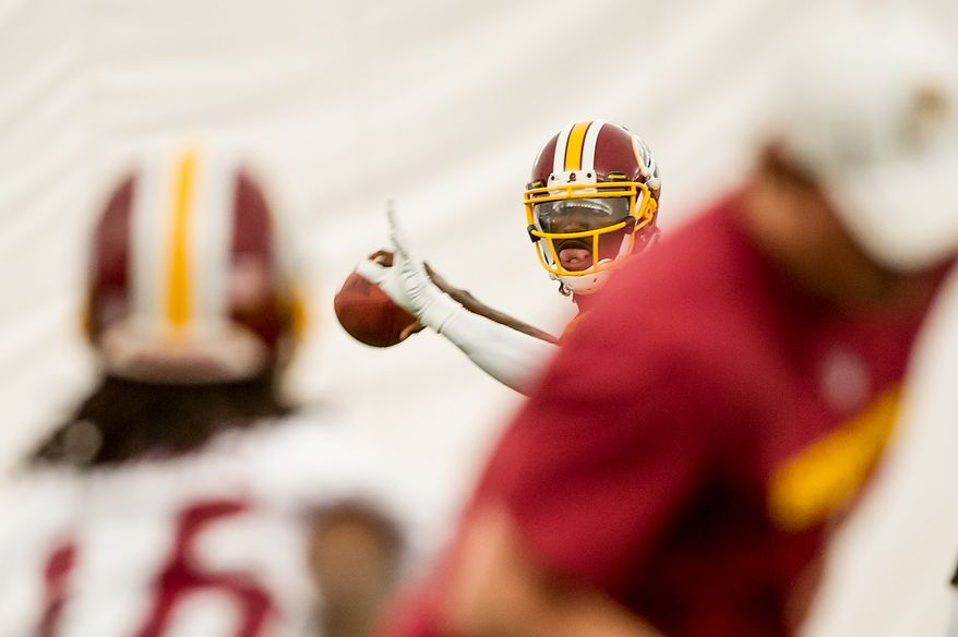 Washington Redskins quarterback Robert Griffin III (10), center, completes a pass in the team's indoor training facility during mini camp at Redskins Park, Ashburn, Va., Tuesday, June 12, 2012. (Andrew Harnik/The Washington Times)