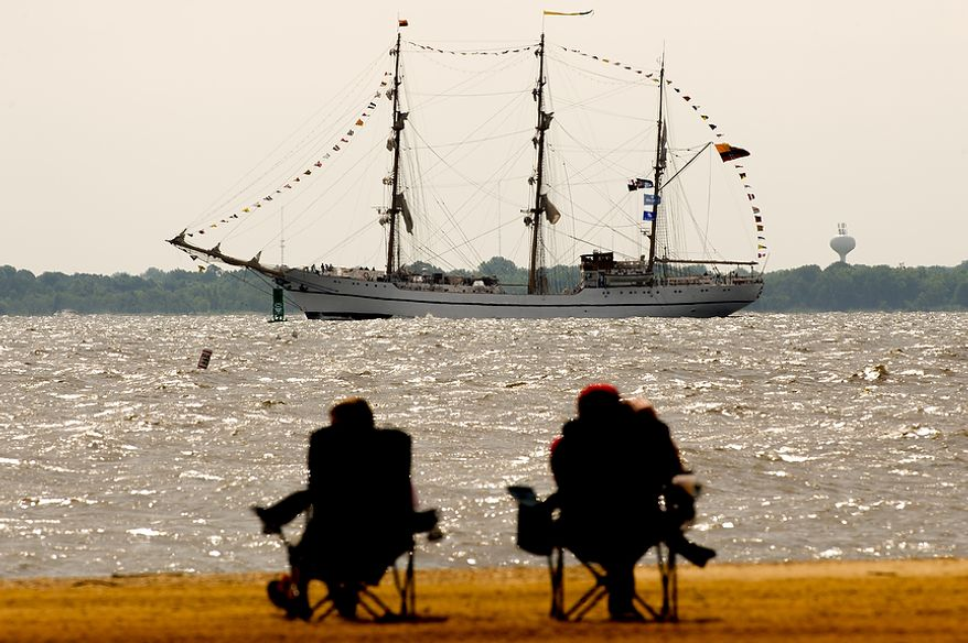 """Beach-goers at Sandy Point State Park in Annapolis, Md., watch June 13, 2012, as tall ships pass under the Chesapeake Bay Bridge en route to the Inner Harbor in Baltimore for a bicentennial commemoration of the War of 1812. The week-long """"Star-Spangled Sailabration"""" includes free tours of the ships, waterside festivities, an air show featuring the Blue Angels and the world premiere of """"Overture for 2012,"""" composed by Philip Glass. (Andrew Harnik/The Washington Times)"""