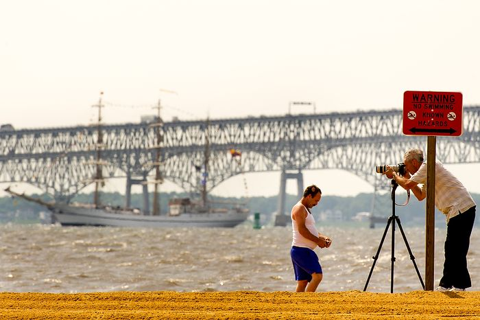 """Joe Hennessy (right) of Adelphi, Md., takes photographs June 13, 2012, from the beach at Sandy Point State Park in Annapolis, Md., of tall ships passing under the Chesapeake Bay Bridge en route to the Inner Harbor in Baltimore for a bicentennial commemoration of the War of 1812. The week-long """"Star-Spangled Sailabration"""" includes free tours of the ships, waterside festivities, an air show featuring the Blue Angels and the world premiere of """"Overture for 2012,"""" composed by Philip Glass. (Andrew Harnik/The Washington Times)"""
