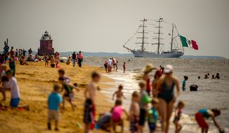 "Revelers line the beach at Sandy Point State Park in Annapolis, Md., on June 13, 2012, as tall ships pass under the Chesapeake Bay Bridge en route to the Inner Harbor in Baltimore for a bicentennial commemoration of the War of 1812. The week-long ""Star-Spangled Sailabration"" includes free tours of the ships, waterside festivities, an air show featuring the Blue Angels and the world premiere of ""Overture for 2012,"" composed by Philip Glass. (Andrew Harnik/The Washington Times)"