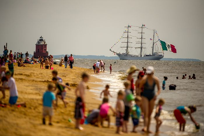 """Revelers line the beach at Sandy Point State Park in Annapolis, Md., on June 13, 2012, as tall ships pass under the Chesapeake Bay Bridge en route to the Inner Harbor in Baltimore for a bicentennial commemoration of the War of 1812. The week-long """"Star-Spangled Sailabration"""" includes free tours of the ships, waterside festi"""