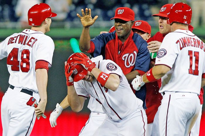 Washington Nationals' Bryce Harper, center, celebrates with teammates after his scored the winning run during the 12th inning of a baseball game against the New York Mets, Tuesday, June 5, 2012, in Washington. The Nationals won 7-6. (AP Photo/Alex Brandon)