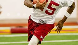 Washington Redskins running back Tim Hightower takes the ball up field in the team's indoor training facility during mini camp at Redskins Park, Ashburn, Va., on Tuesday, June 12, 2012. (Andrew Harnik/The Washington Times)