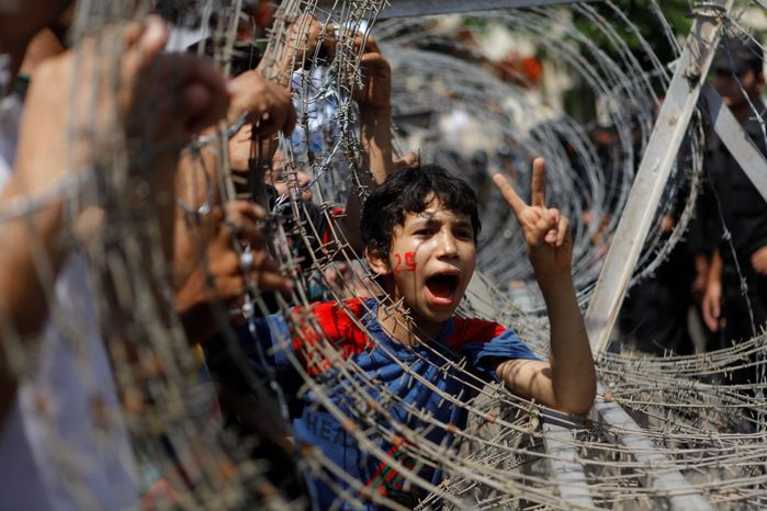 An Egyptian boy peers through barbed wire Thursday during a protest in Cairo. Egypt's high court ruled that the nation's parliament must be dissolved. (Associate Press)