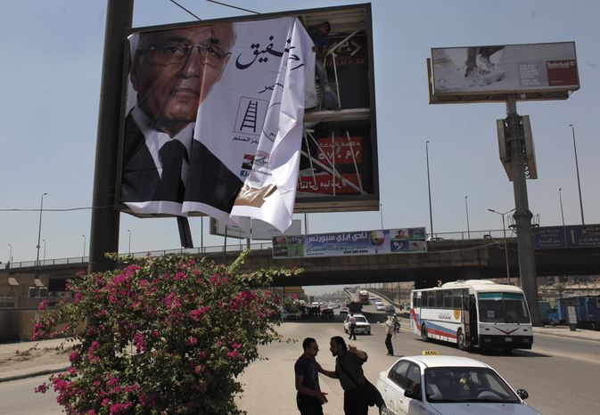 """A laborer installs an election poster for Egyptian presidential runoff candidate Ahmed Shafiq on the side of a highway in Cairo on Monday, June 11, 2012. The Arabic, partially shown, translates as """"Ahmed Shafiq, President for Egypt."""" (AP Photo/Nasser Nasser)"""