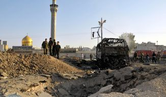 Syrian soldiers stand at the site of a car bombing near the shrine of Sayyida Zeinab (background) in suburban Damascus, Syria, on Thursday, June 14, 2012. (AP Photo/SANA)