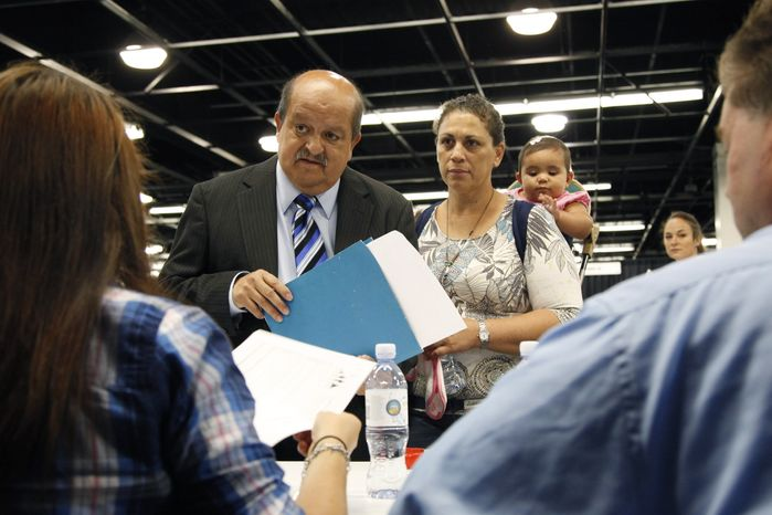 Jose Canales (left), accompanied by his wife, Magdel, and daughter Alexamarie, talks with a recruiter at a job fair in Anaheim, Calif., on Wednesday, Ju