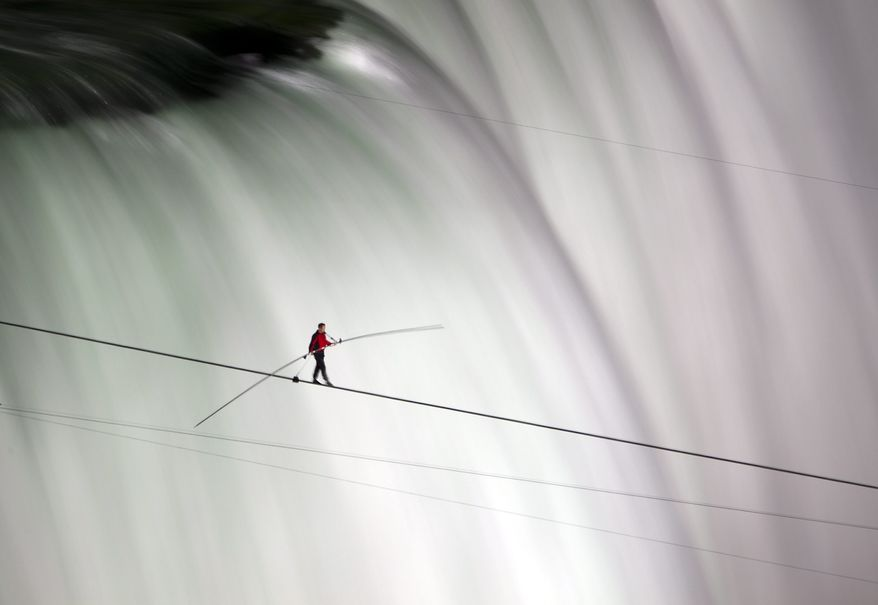 Nik Wallenda walks over Niagara Falls on a tightrope in Niagara Falls, Ontario, on Friday, June 15, 2012. Wallenda has finished his attempt to become the first person to walk on a tightrope 1,800 feet across the mist-fogged brink of roaring Niagara Falls. The seventh-generation member of the famed Flying Wallendas had long dreamed of pulling off the stunt, never before attempted. (AP Photo/The Canadian Press, Frank Gunn)