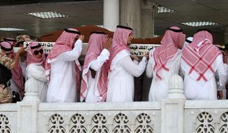 Relatives from the Saudi royal family carry the shrouded body of Crown Prince Nayef Abdul-Aziz inside the Grand Mosque in the Saudi holy city of Mecca on Sunday. The aged king of Saudi Arabia led a burial ceremony Sunday for his brother before his internment following evening prayers. (Associated Press)