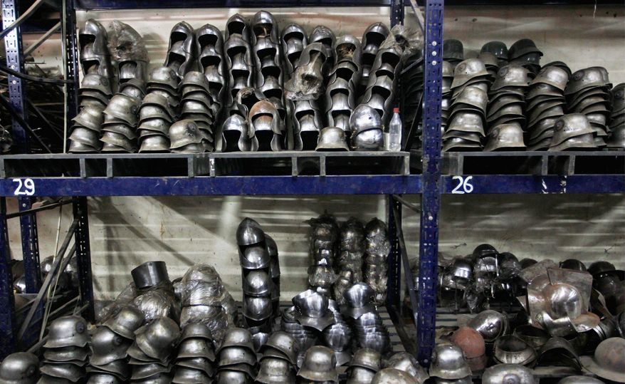 """Finished helmets prepared for Hollywood period movies and re-enactment events are stacked. Ashok Rai's factory has supplied replica military gear for the Russell Crowe movie """"Robin Hood"""" and the Orlando Bloom movie about the Crusades, """"Kingdom of Heaven,"""" among others. (Associated Press)"""