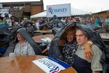 Supporters of Mitt Romney wait in the rain for the former Massachusetts governor's arrival for a campaign event Sunday in the Cleveland suburb of Brunswick, Ohio. (Associated Press)