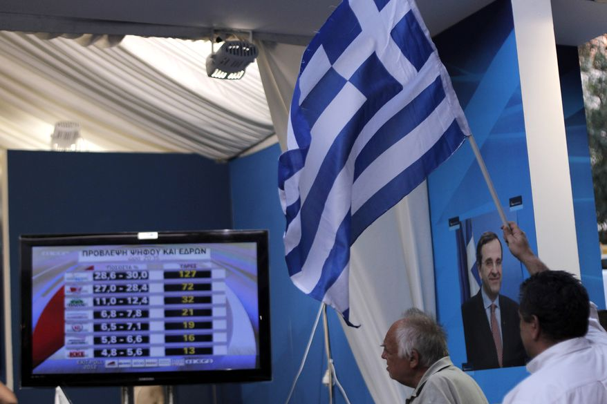New Democracy conservative party supporters wave a Greek flag as a TV screen shows results at an election kiosk at Syntagma square in Athens, Sunday, June 17, 2012. The pro-bailout New Democracy party came in first Sunday in Greece's national election, and its leader has proposed forming a pro-euro coalition government.(AP Photo/Petros Giannakouris)