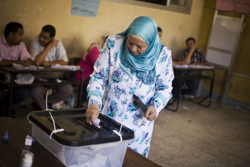 An Egyptian casts her vote at a polling station in Alexandria, Egypt, on Sunday, June 17, 2012, the second day of the nation's presidential runoff election. (AP Photo/Manu Brabo)