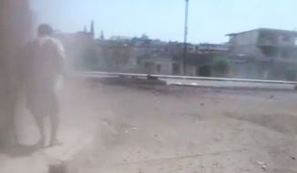 This image made from amateur video released by Ugarit News and accessed on Sunday, June 17, 2012, purports to show a Syrian man standing in smoke from rockets that hit a building in Rastan town in Syria's Homs province. (AP Photo/Ugarit News via AP Video)